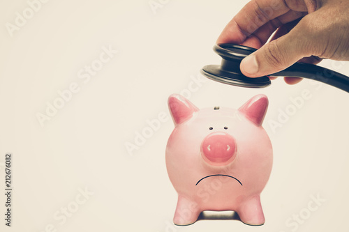 Photo  Hand holding a stethoscope over a sad pink piggy bank isolated