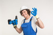 Studio portrait of happy builder laughing at camera with screwdriver wearing gloves and white helmet.