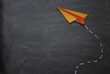 Top view image of paper plane over classroom blackboard background.