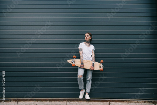 Fotografia, Obraz  distant view of young woman with tattoos holding skateboard against black wall