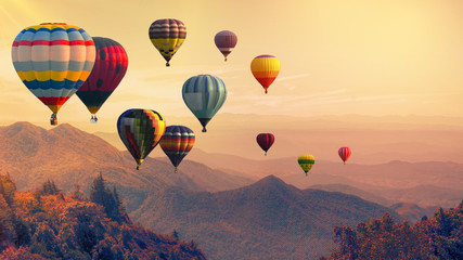 Balon na gorące powietrze nad wysoką górą o zachodzie słońca