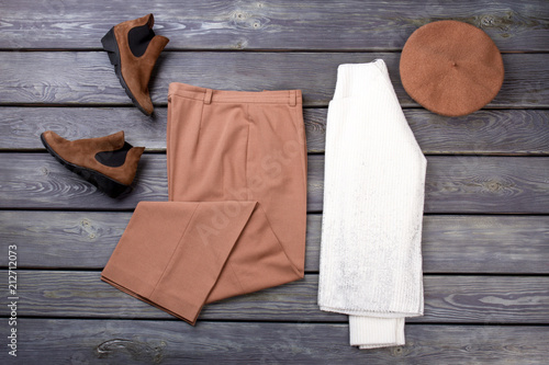 Flat lay warm clothing arrangement. Top view female outfit. Grey wooden surface background.