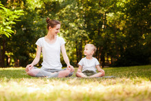 Mom And Son Are Practicing Yoga In The Park.