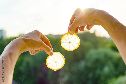 Lemon slices in hand against the sky, silhouette of the city, sunset