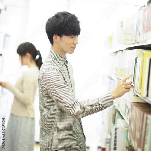 図書館で本を選ぶ男性