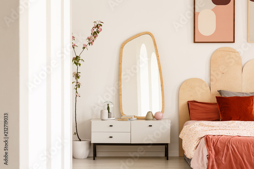 Plant next to white dressing table with mirror in red bedroom interior with poster above bed Wallpaper Mural