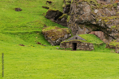 Fotobehang Cappuccino Old hut with green roof in the rock in Iceland