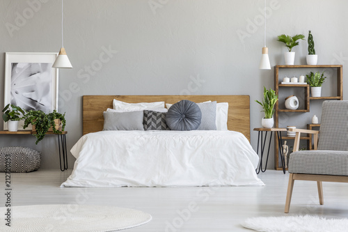 Photo  Patterned armchair in grey bedroom interior with poster on table with plants next to bed