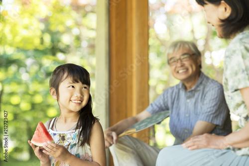 縁側でスイカを食べる女の子と祖父母