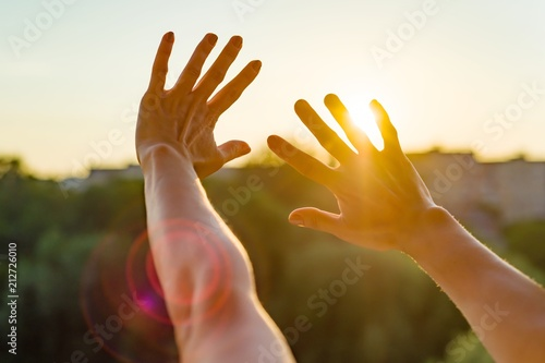 Valokuva  Hands open to the sunset, meditation, the background of the open window in the h
