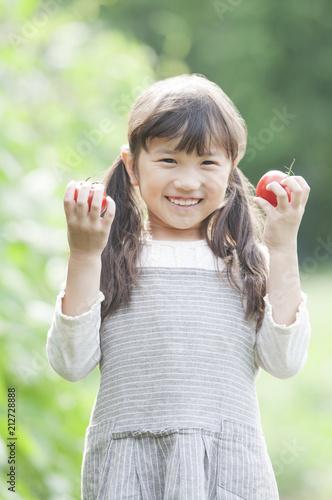 畑でトマトを持ち微笑む女の子