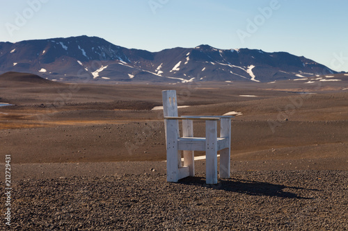 Foto op Plexiglas Diepbruine Creative large wooden chair on a stony rocky desert landscape of Iceland