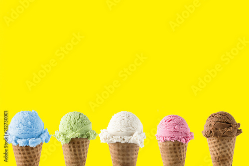 Variety of ice cream flavor in cones blueberry ,strawberry, green tea, chocolate and coconut setup on yellow background . Summer and Sweet menu concept.