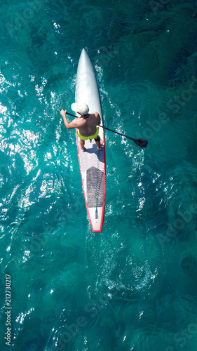 Fototapeta Aerial drone bird's eye view of man exercising sup board in turquoise tropical c