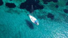 Aerial Drone Birds Eye View Of Sail Boat Docked In An Ionian Island With Crystal Clear Emerald Sea, Greece