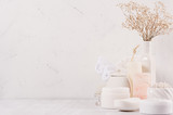 Natural spa cosmetics with white cream, clay, salt, soap and small dry flowers on white wood background, interior, border.