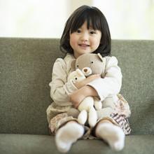 ソファーでぬいぐるみを抱き微笑む女の子