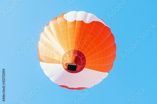 Fotobehang Ballon Colorful unbranded hot-air balloon flying in the background of blue sky, low angle picture