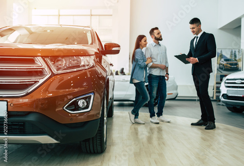 Obraz Young modern happy couple buying a new car in city dealership and talking with salesman - fototapety do salonu