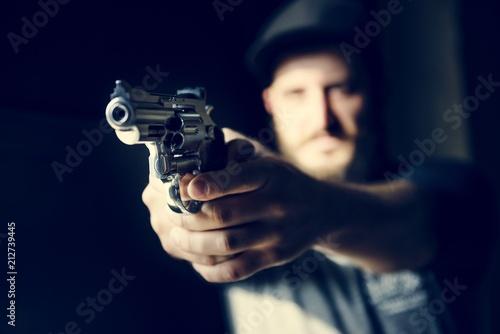 Stampa su Tela Man holding a gun with black background
