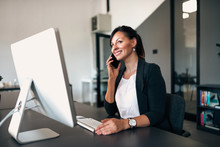 Businesswoman Making Call While Sitting At Office In Front Of Computer.