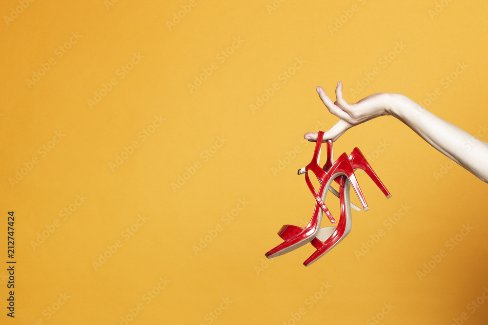 Fototapeta Hand with high hell shoes in studio on yellow background