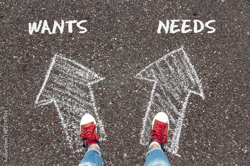 Photo  Chalky arrows Wants and Needs with feet in red sneakers from above standing on asphalt