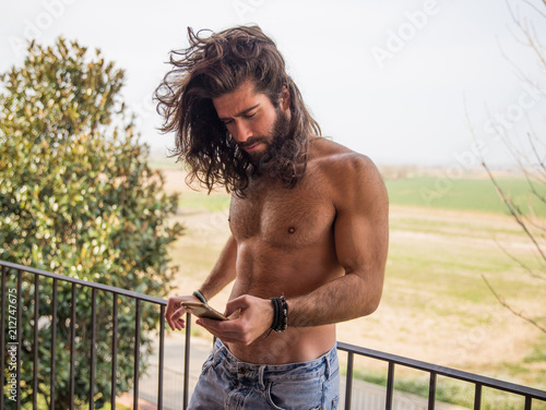 Fotografie, Obraz  Young man with long hair being in a terrace