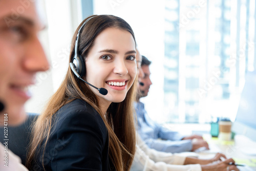 Carta da parati Smiling friendly woman working in call center office with team as the customer c
