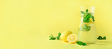 Detox water with mint, lemon on yellow background. Banner with copy space. Citrus lemonade. Summer fruit infused water.