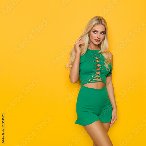Valokuva  Beautiful Blond Woman In Green Short Jumpsuit Is Looking Away