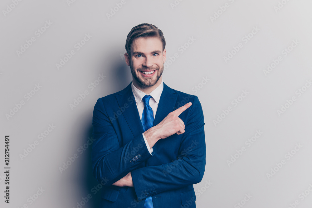 Fototapeta Portrait with copy space for advertisement, product of cheerful, positive, trendy man with hairstyle, stubble showing with forefinger empty place, isolated on grey background, looking at camera