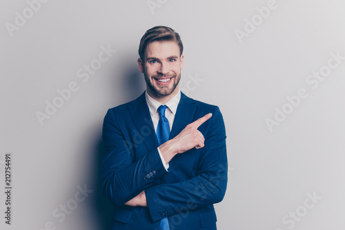 Obraz Portrait with copy space for advertisement, product of cheerful, positive, trendy man with hairstyle, stubble showing with forefinger empty place, isolated on grey background, looking at camera - fototapety do salonu