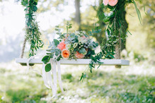 Wedding Bouquet Of Beige And Pink Roses Outdoors On The Decorated Swing