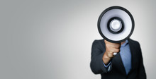 Announcement - Businessman With Megaphone In Front Of Face On Gray Background