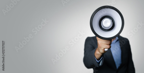 Photo announcement - businessman with megaphone in front of face on gray background