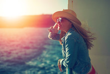 Young Traveler Woman On Sea In Hat Looking Away In Sunset