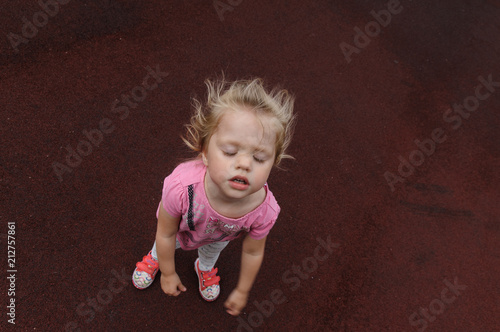 capricious little girl on a dark red background Tablou Canvas