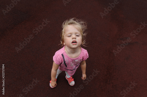 Valokuva  capricious little girl on a dark red background