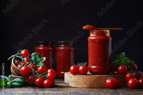Tomato sauce in a glass jar, tomatoes and herbs on its side.
