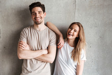 Portrait Of Adorable Caucasian Couple Man And Woman In Basic Clothing Posing Together At Camera With Happy Smile, Isolated Over Concrete Gray Wall Indoor