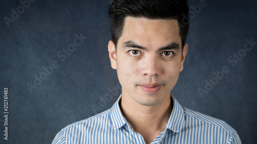 cb28d64d4 Close up Handsome young asia man wearing a blue shirt doing smile and  happiness isolated on