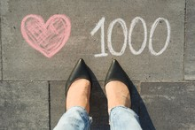 View From Above, Female Feet With Text 1000 Likes In Social Networks Written On Grey Sidewalk.