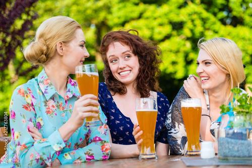 Foto op Aluminium Hoogte schaal Happy friends toasting with beer in garden pub