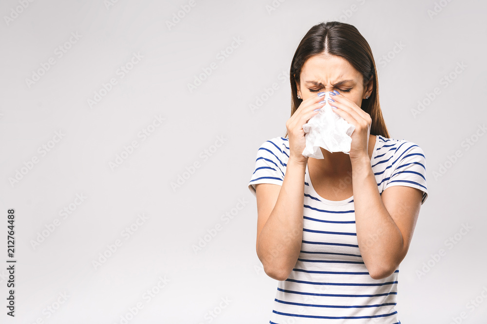 Fototapeta People, healthcare, rhinitis, cold and allergy concept - unhappy woman with paper napkin blowing nose