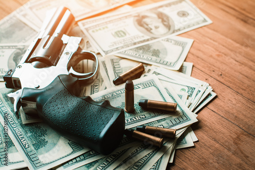 Photo Corruption concept, with guns and dollar bills placed on wooden boards