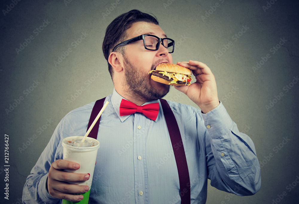Fototapeta Overweight business man eating with appetite a burger holding a can of soda drink