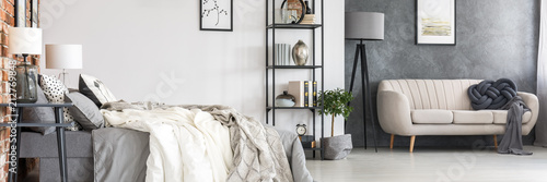 Staande foto Hoogte schaal Black, industrial furniture, comfortable bed and a stylish sofa in a spacious studio sleeping and living room interior in a hipster loft with an orange brick wall