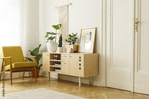 Yellow wooden armchair next to cupboard with plants and poster in retro flat interior Wallpaper Mural