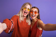 Studio lifestyle portrait of two best friends hipster girls wearing stylish bright orange outfits, dresses and sweater,sunglasses.Two beautiful young women in casual clothes in studio.